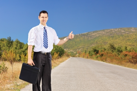 Young businessperson holding a leather suitcase and hitchhiking on an open road photo