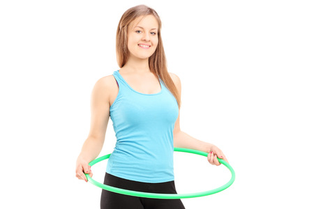 Young female athlete exercising with a hula-hoop isolated on white background photo