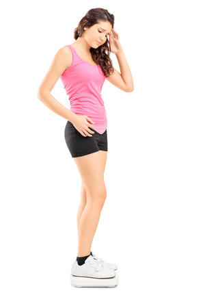 scale model: Full length portrait of a disappointed young female standing on weight scale isolated on white background