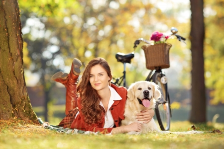 Pretty young female lying down with labrador retriever dog in a park photo