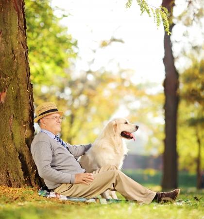 Señor mayor y su perro perdiguero de Labrador sentado en el suelo en un parque, disparó con una inclinación y desplazamiento de lente