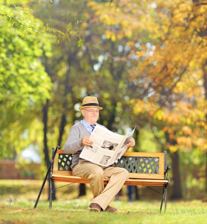 Senior gentleman seated on a wooden bench reading a newspaper in a park, shot with a tilt and shift lens photo