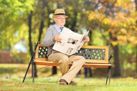 Senior gentleman seated on a wooden bench reading a newspaper in a park photo