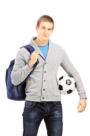mochila escolar: Estudiante masculino joven con mochila sosteniendo una pelota de fútbol aislados sobre fondo blanco