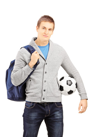 Young male student with school bag holding a football isolated on white background photo