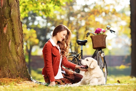 green clothes: Beautiful female sitting on a green grass and looking at her labrador retriever dog in a park