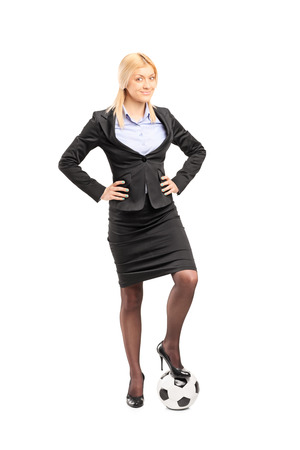 skirt suit: Full length portrait of a young blond businesswoman in high heels posing with a soccer ball isolated on white background