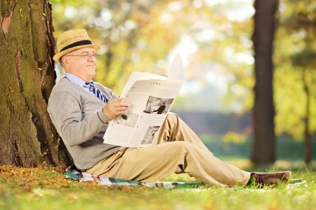 Smiling senior gentleman seated on a grass reading a newspaper in a park at autumn photo