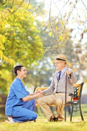 Maschio sanitario aiutando uomo anziano seduto su una panchina di legno in un cantiere