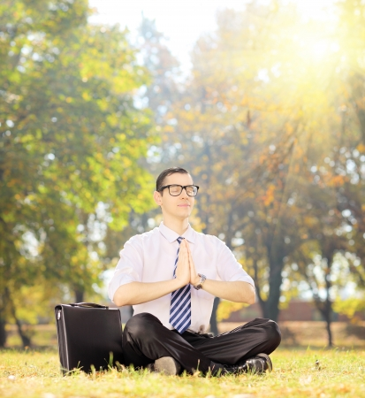 Young businessperson with eyeglasses doing yoga exercise seated on a green grass in a park, shot with a tilt and shift lens photo