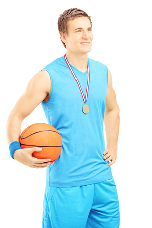 Smiling basketball player posing with a golden medal and basketball isolated on white background photo