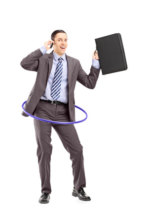 Full length portrait of a young businessman in suit dancing with a hula hoop and talking on a mobile phone isolated on white background photo