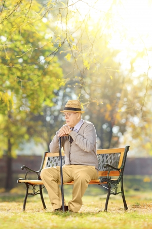 dissappointed: Sad senior gentleman with a cane sitting on wooden bench in a park on a sunny day