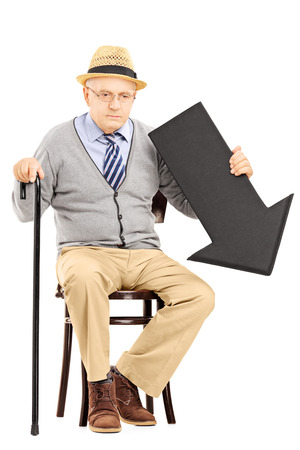 dissappointed: Sad senior man sitting on a wooden bench with big black arrow pointing down isolated on white background