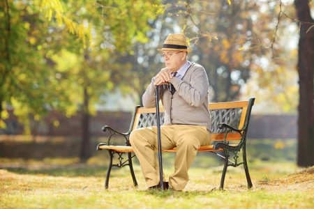 pensions: Sad senior man with cane sitting on a wooden bench in a park on a sunny day
