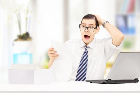 caras emociones: Contador joven sorprendido en su oficina mirando factura muy cara