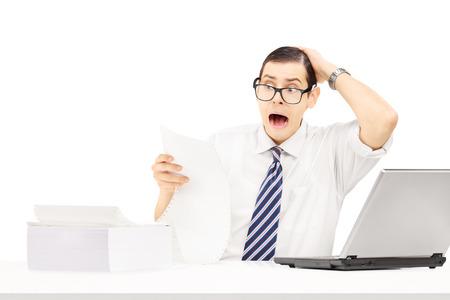 caras emociones: Impresionado joven empresario en su lugar de trabajo mirando factura muy cara aisladas sobre fondo blanco