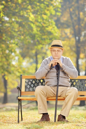 old man sitting: Thoughtful senior man with a cane sitting on a wooden bench in a park on a sunny day