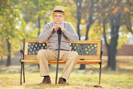 Thoughtful senior man with a cane sitting on wooden bench in a park on a sunny day photo