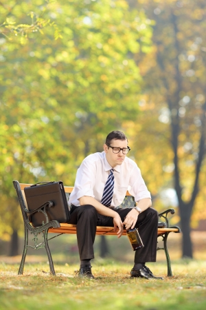 Disappointed young businessman sitting on a wooden bench with bottle in his hand, in a park photo