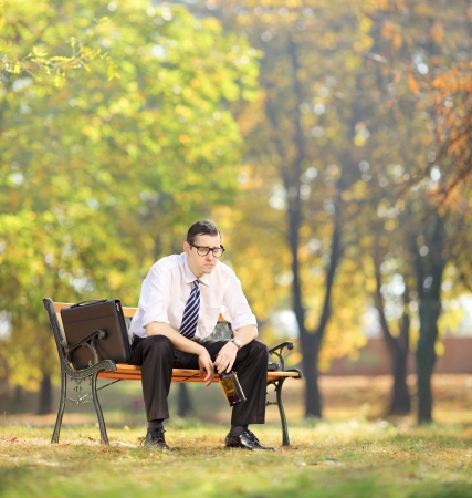 Disappointed young businessman sitting on a wooden bench with bottle in his hand, in park, shot with tilt and shift photo