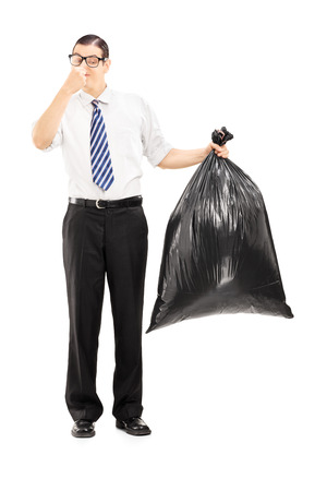 disgusting: Full length portrait of a male closing his nose and holding a stinky garbage bag isolated on white background