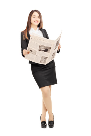 newspaper: Full length portrait of a young businesswoman in black suit leaning on a wall and holding a newspaper isolated on white background