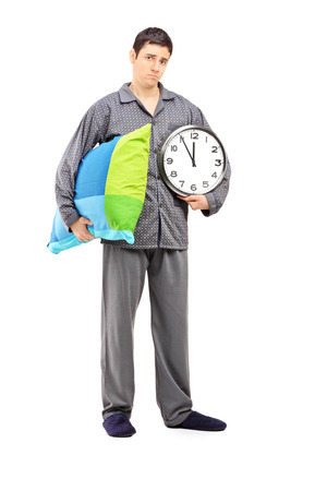 sleepy man: Full length portrait of young sleepy guy holding a wall clock and pillow isolated on white background