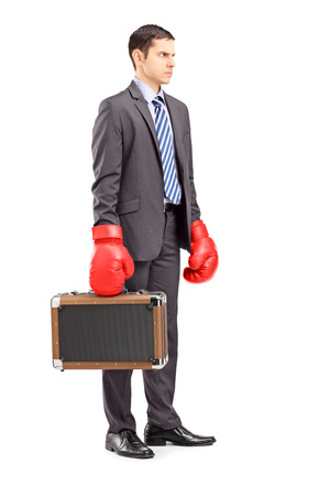 Full length portrait of an angry young businessman holding a briefcase with red boxing gloves isolated on white background photo