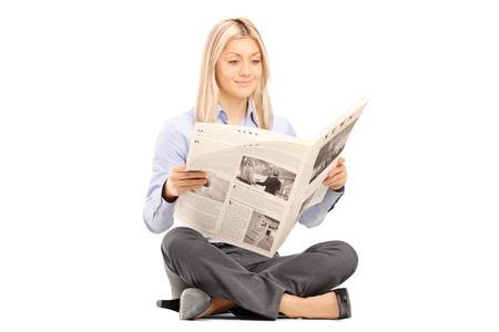 Giovane donna sorridente sittong su un pavimento e leggere il giornale isolato su sfondo bianco Archivio Fotografico - 23578954