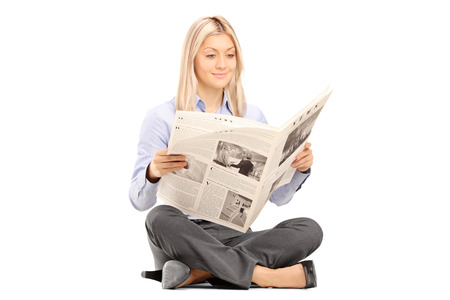 reading: Young smiling woman sittong on a floor and reading a newspaper isolated on white background  Stock Photo