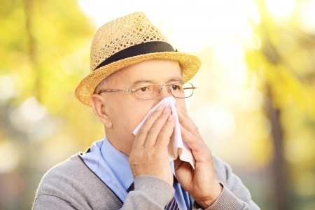 grippe: Mature man blowing his nose in tissue paper because of being ill or allergy outside