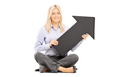 directive: Young blond woman seated on a floor holding a big black arrow isolated on white background