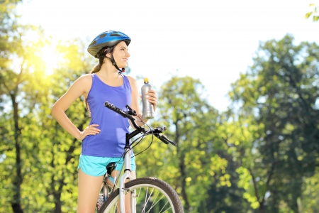 Young female biker posing on a mountain bike outdoor on a sunny day photo
