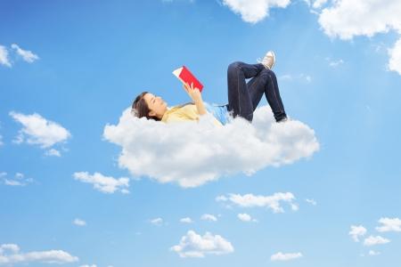 Jeune femme détendu en lisant un roman et couché sur des nuages