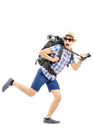 asustado: Retrato de cuerpo entero de un excursionista asustado con la mochila y la c�mara corriendo aislados en fondo blanco