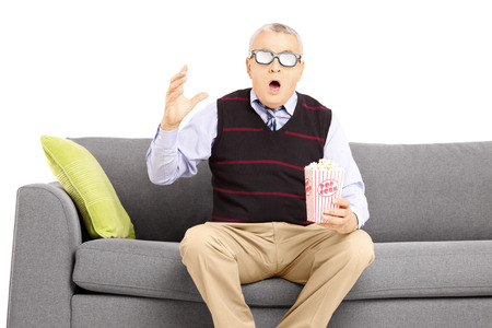 Shocked senior man with popcorn box sitting on a sofa and watching movie isolated on white background photo