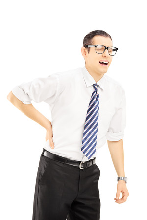 dorsalgia: Young man with tie suffering from a back pain isolated on white background