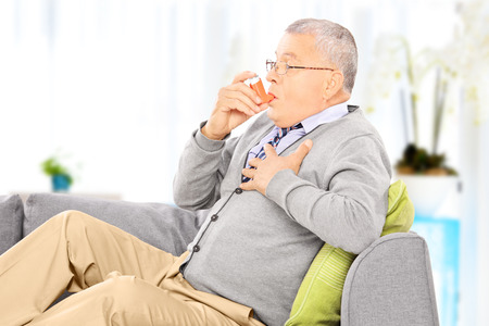 asma: Hombre maduro sentado en un sofá de tomar el tratamiento del asma con el inhalador en casa