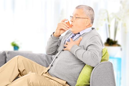 Oudere man zittend op een bank het nemen van de behandeling van astma met inhaler thuis Stockfoto
