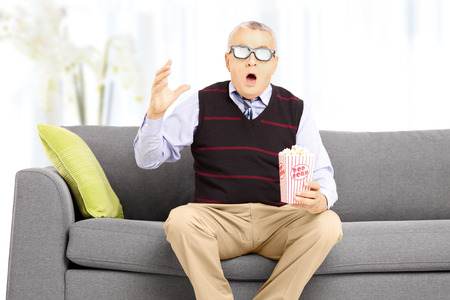 Shocked senior man with popcorn box sitting on a sofa and watching movie at home photo