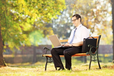 Young smiling businessperson sitting on a wooden bench and working on a laptop in a park photo
