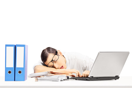 fascicule: Exhausted young businessman sleeping on a desk at his workplace, isolated on white background