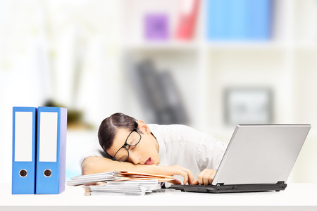 fascicule: Exhausted young businessman sleeping on a desk in his office Stock Photo