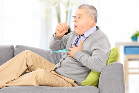 Mature man seated on a sofa coughing because of pulmonary disease at home Stock Photo