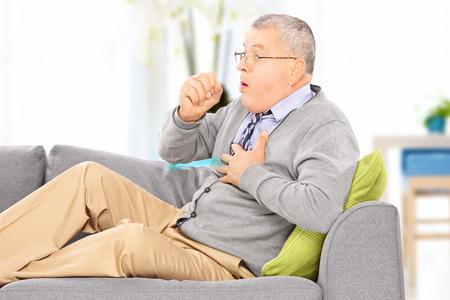 Oudere man zittend op een sofa hoesten vanwege longziekte thuis