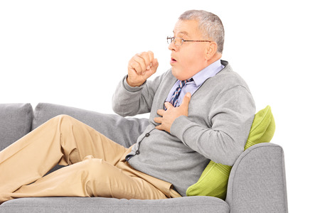 Mature man seated on a sofa coughing because of pulmonary disease isolated on white background
