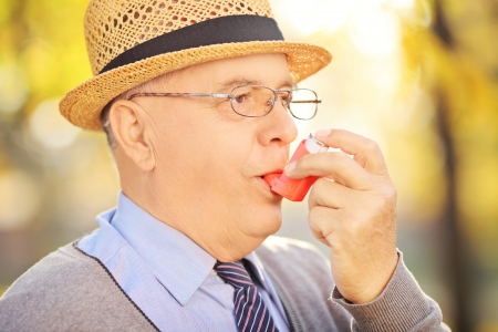 asthmatic: Portrait of senior man taking asthma treatment in a park Stock Photo