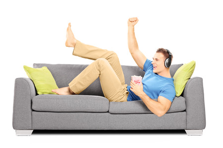 Excited guy lying on a sofa and listening music isolated on white background Stock Photo - 23776649