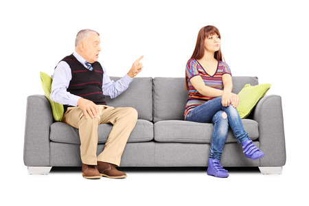 disagreeing: Father reprimending his uninterested daughter seated on a couch isolated on white background Stock Photo